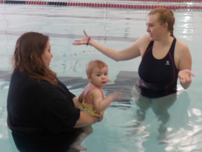 Mother and Baby in the Swimming Pool with Swim Instructor